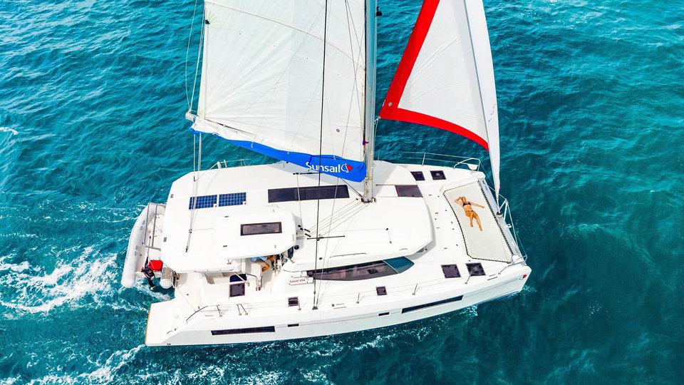 Sunsail yacht sailing on the ocean with sunbather