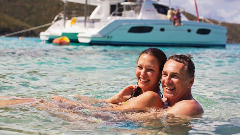 couple-swimming-infront-of-yacht