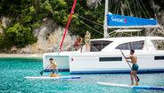 Stand Up Paddling Next To Catamaran At Corfu Island Greece